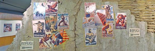 Una paret de formigó mig destruïda, amb tot de cartells propagandístics de la guerra civil espanyola. És la paret exterior de l'escenografia del refugi antiaeri de la tercera planta de l'exposició permanent