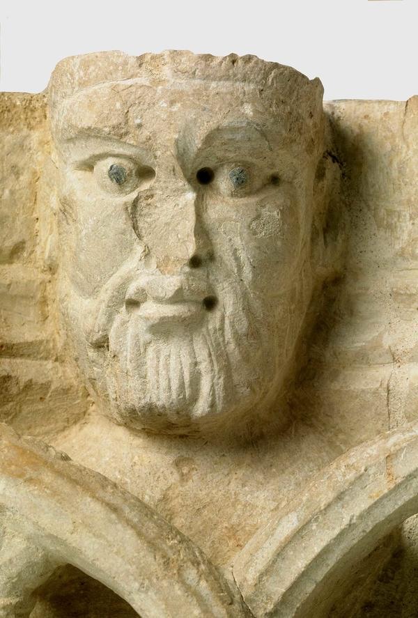 Detall d'una de les fesomies masculines del capitell