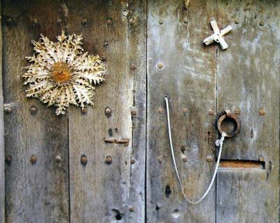 Una porta de fusta antiga amb una cardellina i una creu feta de palma